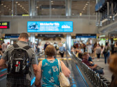 Man and woman stand on moving walkway a busy airport terminal