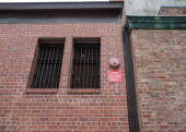 Fire alarm bell hanging outside of brick building