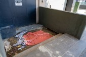 Filth, discarded trash, blankets and towels outside of door labeled no entry