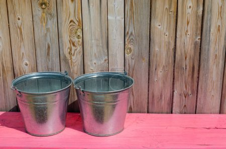 Two metal buckets of water. Pink wooden bench. Rus...