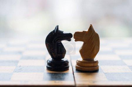 Face contre terre. Pièces d'échecs chevaliers face à face pour une confrontation sur l'échiquier avec fond bleu. Les chevaliers des échecs se confrontent. Chevaliers d'échecs tête à tête.