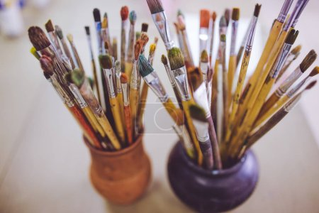 Photo for A bunch of art brushes standing in ceramic vases, on the table in the art studio. - Royalty Free Image