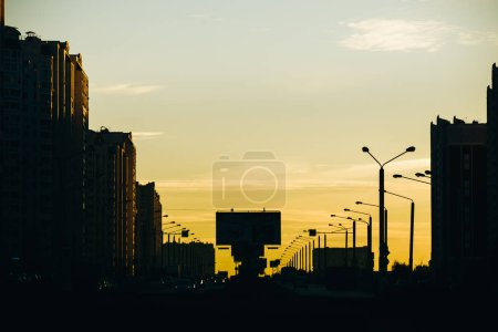Photo for Road and residential buildings in city at sunset. - Royalty Free Image