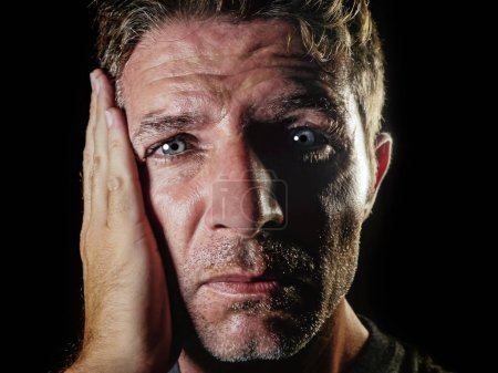 Photo for Close up portrait of sad and depressed man with hand on face looking desperate feeling frustrated and helpless in depression and sadness facial expression concept isolated black bg - Royalty Free Image