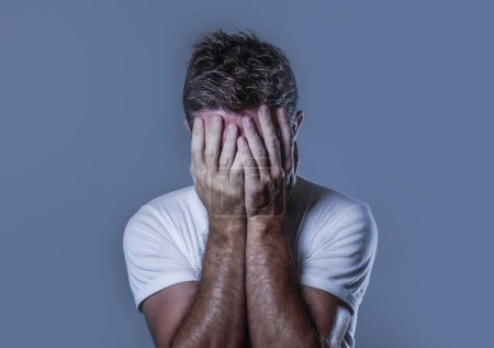 Photo for Portrait of sad and depressed man covering face with hands looking desperate feeling frustrated and helpless in depression and sadness facial expression concept isolated grey background - Royalty Free Image