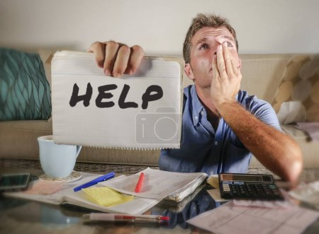 Photo for Young attractive worried and stressed man at home calculating month tax expenses with calculator accounting payments doing bank paperwork in stress looking sad and depressed asking for help - Royalty Free Image