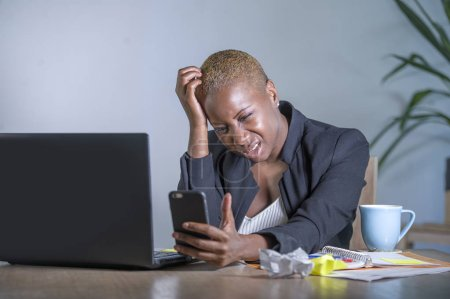 Photo for Young desperate and stressed african american business woman working at laptop computer desk at office suffering stress problem using mobile phone overwhelmed in work crisis concept - Royalty Free Image