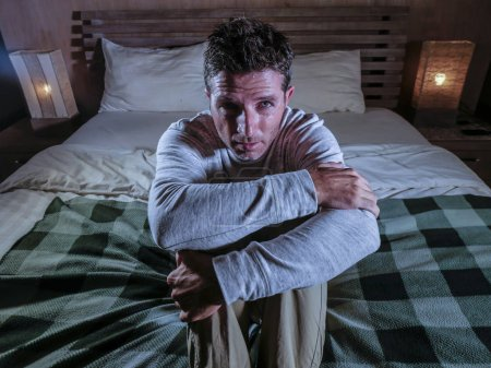 Photo for Indoors portrait of young desperate and depressed man at home bedroom sitting on bed sad and confused suffering pain and depression crying lost feeling sick in mental health and depression - Royalty Free Image