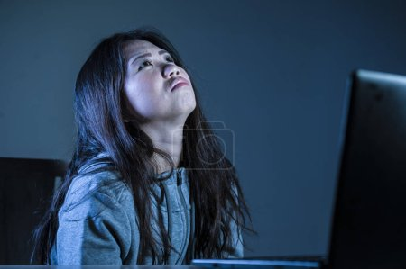 Photo for Young worried Asian Korean student girl looking depressed and desperate studying with laptop computer in stress for exam feeling frustrated stalked and harassed on internet bullying - Royalty Free Image