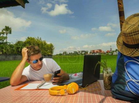 Photo pour Jeune homme nomade numérique attrayant travaillant en ligne en plein air avec ordinateur portable et téléphone mobile en tant que pigiste et emploi indépendant dans le travail indépendant Internet et entrepreneur - image libre de droit