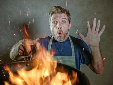 Photo for Young funny and messy home cook man with apron in shock holding pan in fire burning the food in kitchen disaster and unskilled unexperienced terrible home cook at domestic cooking mess - Royalty Free Image