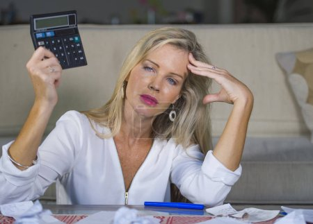Photo for Attractive worried and desperate blond woman calculating domestic money expenses doing paperwork and bank bills accounting with calculator suffering stress in financial problem and depression - Royalty Free Image