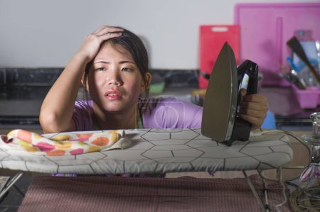 Photo for Portrait of young pretty frustrated and stressed Asian Chinese woman working at home kitchen ironing clothes desperate and overwhelmed in house maid service housework domestic stress - Royalty Free Image