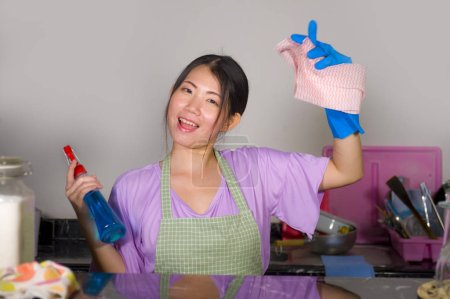 Photo for Young beautiful and happy Asian Chinese woman cleaning and washing with spray bottle at home kitchen in rubber gloves enjoying domestic chores in cheerful and positive housekeeping - Royalty Free Image