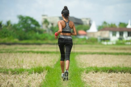 Photo for Back view of young runner woman with attractive and fit body in running outdoors workout at beautiful off road track green landscape background jogging in fitness and healthy lifestyle - Royalty Free Image