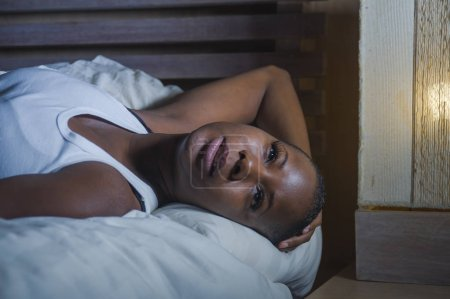 Photo for Young sad and depressed black african American woman in bed sleepless late night feeling desperate looking worried and anxious suffering depression problem and insomnia sleeping disorder - Royalty Free Image