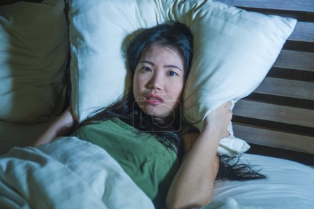 Photo for Lifestyle night portrait of young beautiful scared and stressed Asian Chinese woman lying awake in bed sleepless covering head with pillow suffering nightmare insomnia disorder and depression - Royalty Free Image