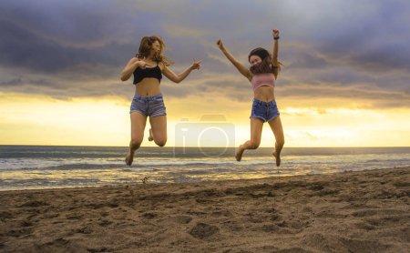 Foto de Retrato de estilo de vida de dos jóvenes felices y atractivas novias asiáticas mujeres coreanas saltando en la playa puesta de sol muy contento y alegre disfrutando de vacaciones de verano viajan juntos sin preocupaciones - Imagen libre de derechos