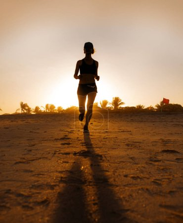 Photo for Silhouette of young attractive and fit runner woman with athletic body running on beautiful Summer sunset light training jogging workout outdoors at tropical beach in fitness wellness and healthy lifestyle - Royalty Free Image