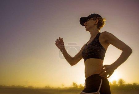 Photo pour Jeune femme coureuse séduisante et en forme avec un corps athlétique en cours d'exécution sur la belle lumière du coucher du soleil été entraînement jogging séance d'entraînement en plein air à la plage tropicale dans la forme physique bien-être et mode de vie sain - image libre de droit