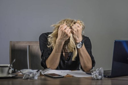 Photo for Young frustrated and stressed business woman crying sad at office desk working with laptop computer overwhelmed by paperwork workload covering her face desperate suffering depression - Royalty Free Image