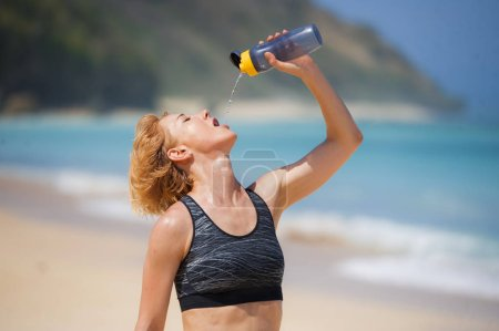 Photo for Young happy and attractive sport runner woman drinking water bottle or isotonic drink after running workout at tropical paradise beach showing fit and athletic body in healthy lifestyle concept - Royalty Free Image