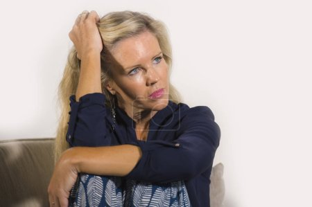 Photo for 40s depressed and anxious beautiful blonde woman suffering depression feeling frustrated and lonely sitting at home sofa couch thoughtful and pensive in middle age crisis and life problem - Royalty Free Image