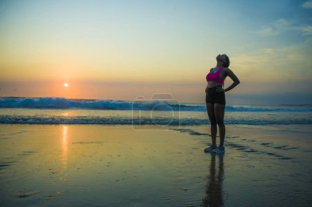 young sporty and tired African American runner woman cooling off breathing exhausted after running workout at beautiful beach sunset in healthy outdoors fitness activity