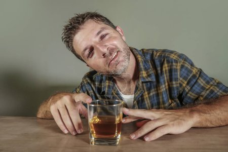 Photo for Young drunk and pissed alcoholic man wasted drinking whiskey glass intoxicated and messy isolated on dark background in alcohol abuse and addiction and alcoholism problem - Royalty Free Image