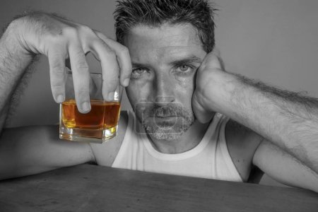 Photo for Isolated black and white portrait of young messy depressed alcoholic man having a drink looking at whiskey glass feeling temptation of alcohol abuse in addiction and alcoholism problem - Royalty Free Image