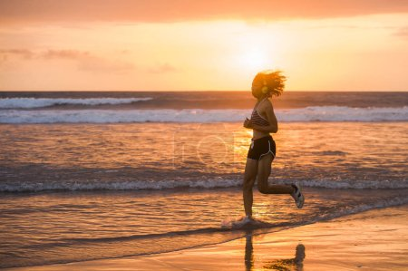 Photo for Silhouette of fit and athletic Asian Chinese sporty woman running on beautiful beach doing jogging workout on sunset in fitness healthy lifestyle and summer outdoors activity concept - Royalty Free Image