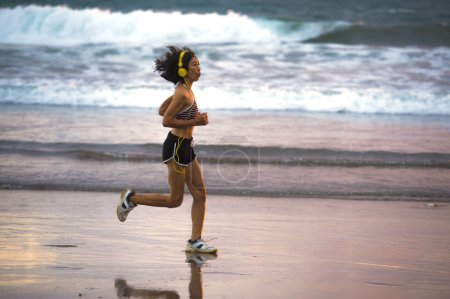 Photo for Fit and athletic Asian Chinese sporty woman running on beautiful beach doing jogging workout on sunset in fitness healthy lifestyle and summer outdoors activity concept - Royalty Free Image