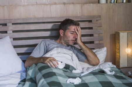 young sick wasted and exhausted man at home bed lying feeling unwell suffering cold and flu sneezing nose with tissues having virus and headache in domestic health care and grippe concept
