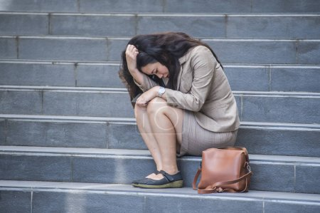 Photo for Young depressed and desperate Asian Korean business woman crying alone sitting on street staircase suffering stress and depression crisis being victim of mobbing or fired losing her job - Royalty Free Image
