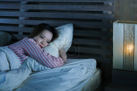 Photo for Young beautiful sad and depressed Asian Korean girl lying on bed late night awake looking thoughtful suffering insomnia sleeping disorder feeling tired and worried in woman depression concept - Royalty Free Image