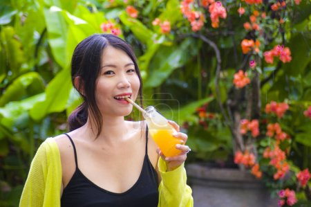 Photo for Young attractive and happy Asian Korean girl having fun in garden outdoors drinking healthy orange juice with straw playful having fun in carefree woman enjoying holidays concept - Royalty Free Image