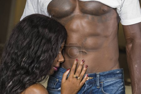Photo for Portrait of young attractive and happy black African American woman touching afro man ripped abdomen showing nude torso and six pack abdominals in fit sexy body worship - Royalty Free Image