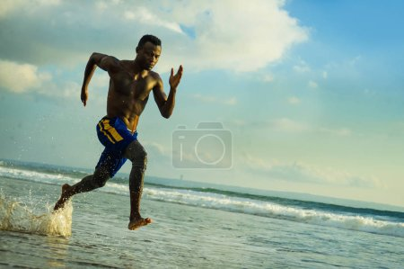 Photo for Young attractive fit athletic and strong black afro American man running at the beach training hard and sprinting on sea water in professional athlete lifestyle and ripped runner workout - Royalty Free Image