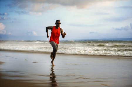 Photo for Young attractive fit athletic and strong black African American man running at the beach training hard and sprinting on sea water in professional athlete lifestyle and ripped runner workout - Royalty Free Image