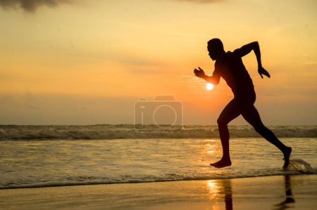 Photo pour Silhouette de séduisantes jeunes forme athlétique et fort noir afro-américain fonctionnant à la formation de plage coucher de soleil dure et sprint sur l'eau de mer en athlète professionnel et entraînement du coureur - image libre de droit