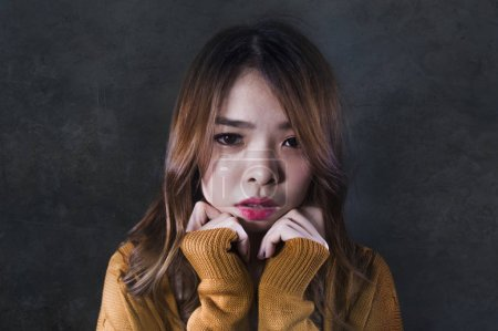 Photo for Young crazy desperate and sad Asian Korean woman looking depressed and helpless feeling anguish and pain on isolated dark background in pain face expression suffering depression - Royalty Free Image