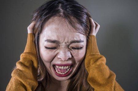 Photo pour Jeune fou désespéré et contrarié asiatique coréen femme criant peur et anxieux sentiment colère et douleur isolé sur fond sombre sur la douleur dramatique visage expression dans la dépression concept - image libre de droit