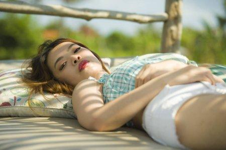 Photo pour Jeune belle et sexy asiatique coréen couché confortable à vacances station jardin lit ayant bronzage détendu et refroidi en vacances d'été et concept de beauté - image libre de droit