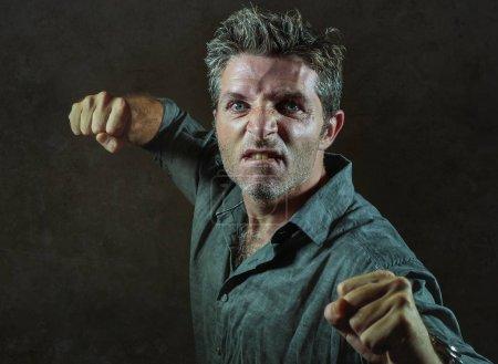 Photo pour Jeune homme contrarié et agressif dans le pub élever poing menaçant coup de poing prêt à se battre comme le truand violent fauteur de troubles et furieux gaspillé gars isolé sur fond sombre - image libre de droit