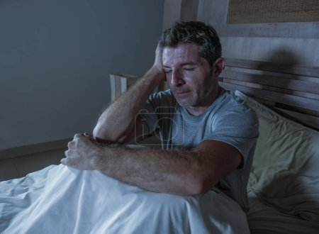Photo for Young sad and depressed sleepless man lying on bed worried and thoughtful at home bedroom suffering depression problem feeling unwell and desperate  broken heart after relationship divorce - Royalty Free Image