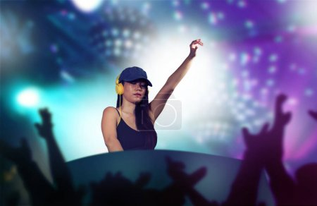 Photo pour Young attractive and happy Asian Japanese DJ woman remixing techno music using deejay gear and headphones at night club with lights background in clubbing fun and night lifestyle concept - image libre de droit