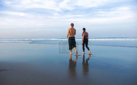 Photo for Lifestyle back portrait of young attractive and healthy couple relaxed walking on beautiful desert beach early morning in romantic trip enjoying holidays Summer together - Royalty Free Image