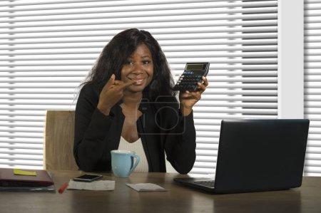 Photo pour Verticale d'affaires d'entreprise de jeune belle et confiante femme d'affaires noire afro-américaine travaillant au bureau d'ordinateur de bureau souriant retenant la calculatrice dans le succès financier de femme - image libre de droit