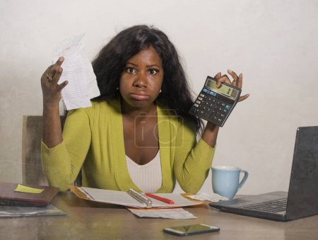 Photo for Young stressed and overwhelmed black African American woman doing domestic accounting with calculator feeling upset and angry holding paperwork in financial stress and business problem - Royalty Free Image