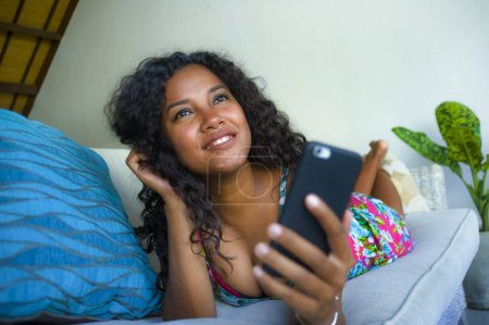 Photo pour Young beautiful and happy mixed ethnicity Caucasian and black African American woman lying at home couch using mobile phone app dating online smiling cheerful and relaxed - image libre de droit